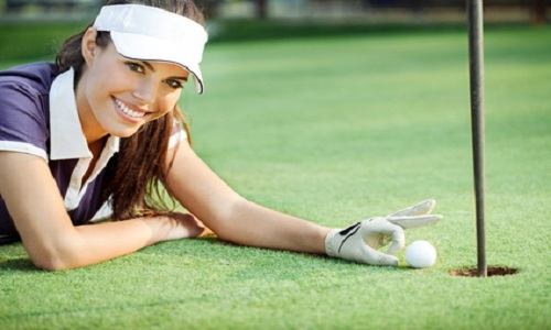 Happy young woman golf pushing golf ball into the hole, lying on green grass